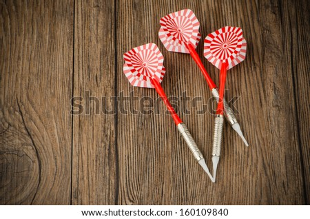 Three arrows darts on old wooden table. - stock photo