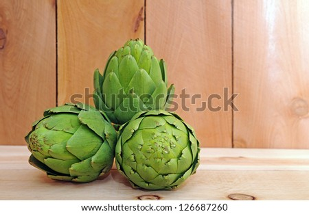 three artichoke on wooden shelf - stock photo