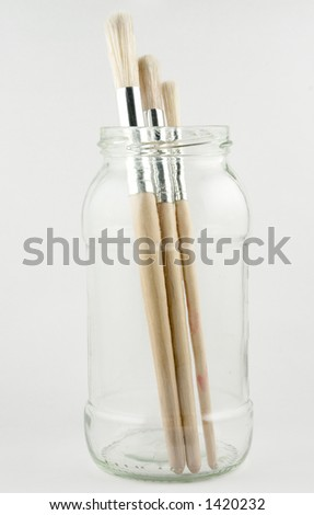 Three artists' paint brushes standing in a jar