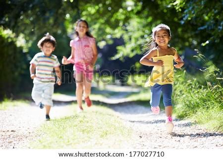 Three Asian Children Enjoying Walk In Countryside - stock photo