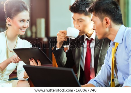 Three Asian Chinese office people or businessmen and businesswoman having a business meeting in a hotel lobby discussing documents on a tablet computer while drinking coffee  - stock photo