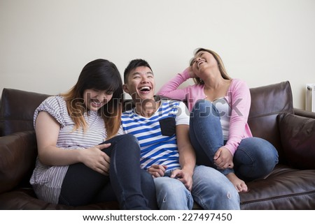 Three Asian friends in sitting room at home, laughing and having fun. - stock photo