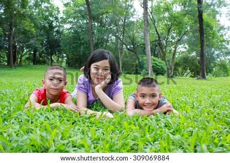 Three asian kids having a good time in the park.