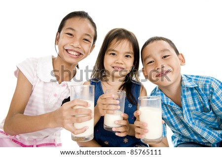three asian kids with glasses of milk, isolated on white background - stock photo