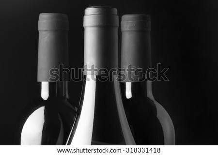Three assorted wine bottles close-up on black background. Monochrome black and white image. Focus on front bottle. - stock photo