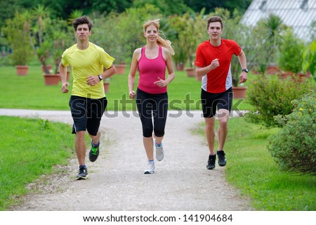 Three athletes jogging in the park