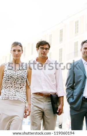Three attractive business people walking together through a classic city square with office buildings in the background during a sunny day. - stock photo