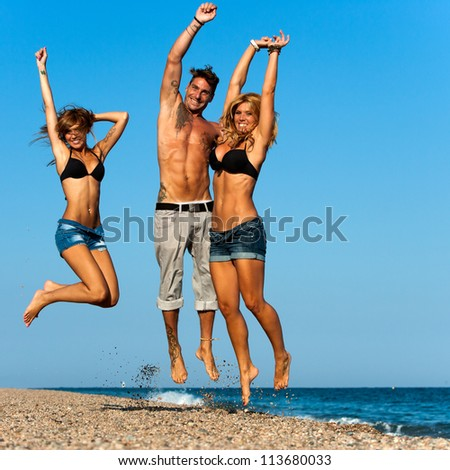 Three attractive energetic friends jumping on beach.