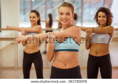Three attractive sport girls smiling while stretching hands in fitness class. Beautiful blonde girl looking at camera - stock photo