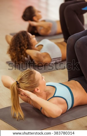 Three attractive sport girls smiling while working out lying on yoga mat in fitness class, back side view - stock photo