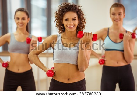 Three attractive sport girls smiling while working out with dumbbells in fitness class - stock photo