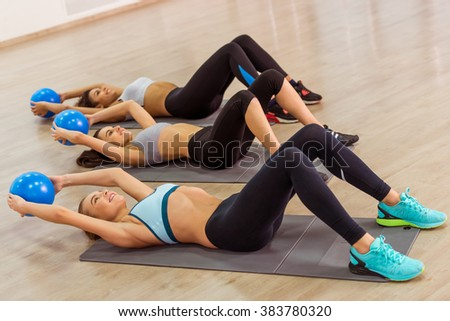 Three attractive sport girls smiling while working out with fitness ball lying on yoga mat in fitness class - stock photo