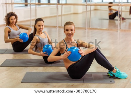 Three attractive sport girls smiling while working out with fitness ball sitting on yoga mat in fitness class - stock photo