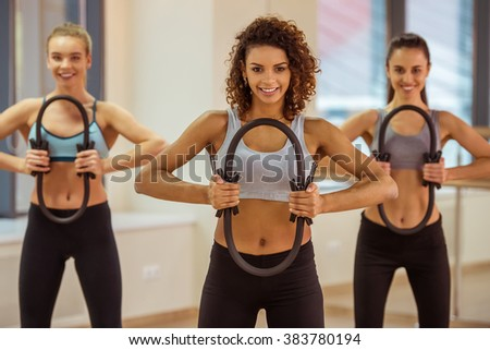 Three attractive sport girls smiling while working out with pilates ring in fitness class - stock photo