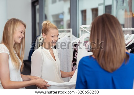 Three attractive stylish young woman shopping in a boutique clothing store looking through the garments on the rails and smiling and chatting - stock photo