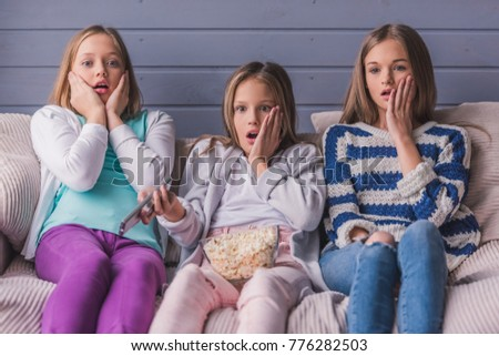 Three attractive teenage girls in casual clothes are eating popcorn and covering their faces while watching TV on couch at home
