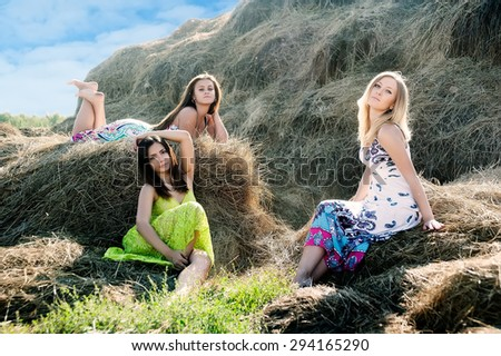 Three attractive women sitting on hay stack - stock photo