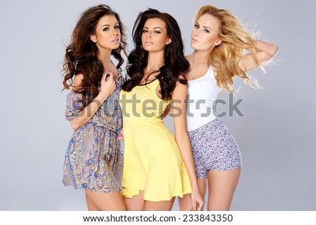 Three Attractive Women with Air Blown Long Wavy Hair Posing in Casual Fashion Outfit While Looking at the Camera. Captured in the Studio with Gray Background.