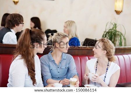 Three attractive young female friends chatting in a cafe sitting enjoying a cup of coffee together - stock photo