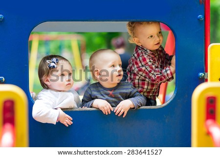 Three babies in the toy car on the playground