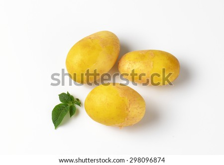 three baby potatoes with leaves on white background
