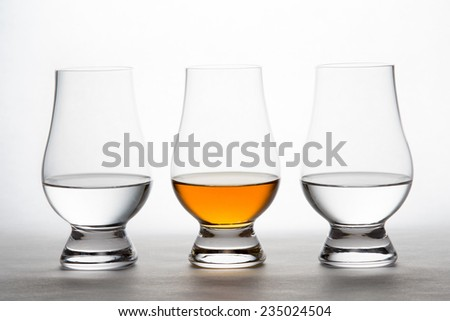 Three backlit crystal glasses containing clear and amber liquor.  Vodka, whiskey, bourbon, brandy, moonshine, etc. - stock photo
