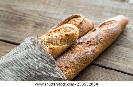 Three baguettes on the wooden background - stock photo