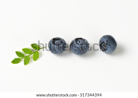 three ball of fresh blueberries with green leaves - stock photo