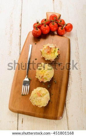 three balls irish colcannon, made with mashed potato, thyme, cabbage, grilled bacon and crushes peppercorn on a wooden board, wet tomatos in the background - stock photo
