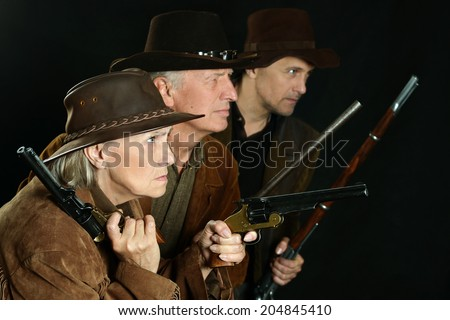 Three bandits with guns in the wild west - stock photo