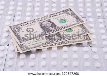 Three banknotes on one dollar lays on a background from tablets - stock photo