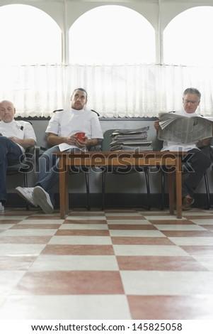 Three barbers waiting for customers in barbershop - stock photo