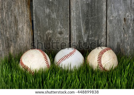 Three baseballs on green grass with room for your type. - stock photo