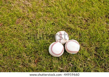 Three baseballs on the green grass of a field