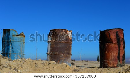 Three battered 55 gallon drums in a row suggest petrochemicals, hazardous waste and leaking industrial products. - stock photo