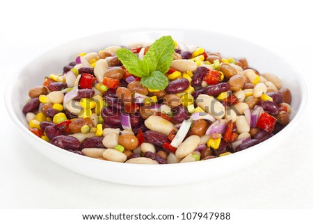 Three bean salad with sweetcorn, roasted red peppers and red onion in a vinaigrette dressing.