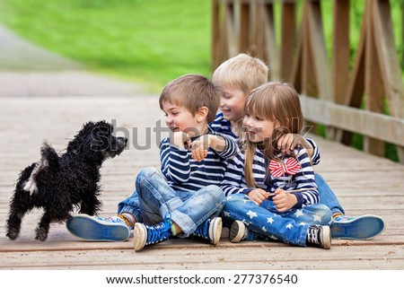 Three beautiful adorable kids, siblings, playing with cute little dog in the park, springtime - stock photo