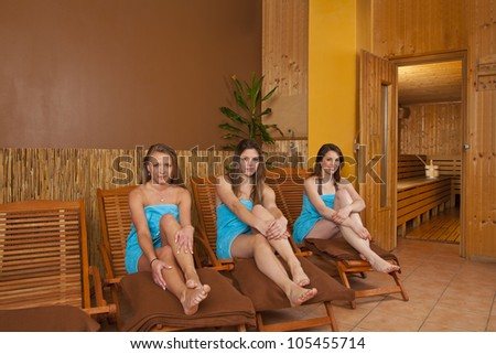 three beautiful and smiling young women sitting on loungers in front of a sauna - stock photo