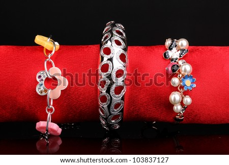 Three beautiful bracelets on the red cloth on black background