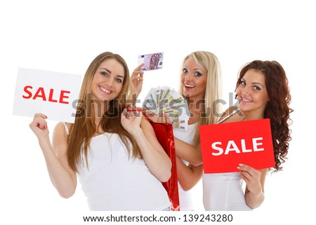 Three beautiful cheerful  girlfriends with sale sign, purchases and money stand on a white background. Shopping.