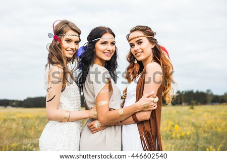 Three beautiful cheerful hippie girls, best friends, the outdoors, cute smile, trendy hairstyles, feathers in her hair, white dress, tattoo flash, gold accessories, Bohemian, bo-ho style fashion indie - stock photo