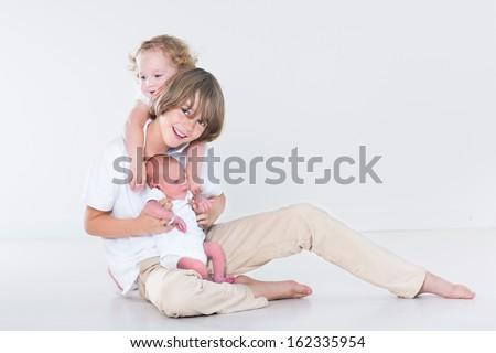 Three beautiful children - teenager boy, toddler girl and a newborn baby - playing together in a white room - stock photo