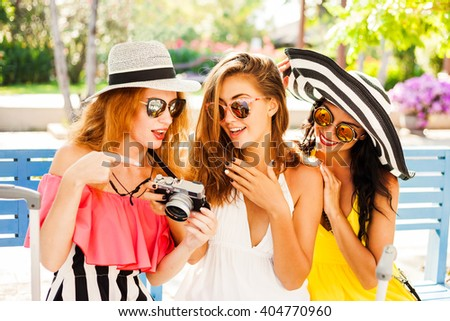 Three beautiful fashion girls sitting with their suitcases and wait in the terminal at the airport. Blonde, redhead, brunette, dressed in bright dresses and hats. - stock photo