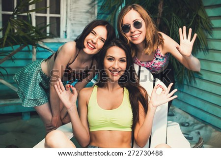 Three beautiful female friends make fun and selfie at beach house neae ocean side at sunset