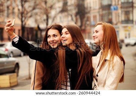 Three beautiful friends having fun outdoor in spring on the street.  Young hipsters women in the city traffic. Outdoors, lifestyle. - stock photo