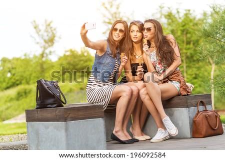 Three beautiful girlfriends make Selfie photo on a bench  - stock photo