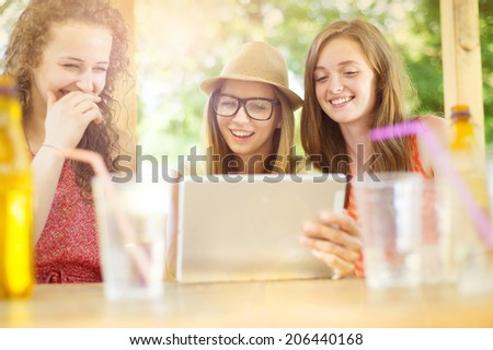 Three beautiful girls drinking and having fun with tablet in pub garden - stock photo