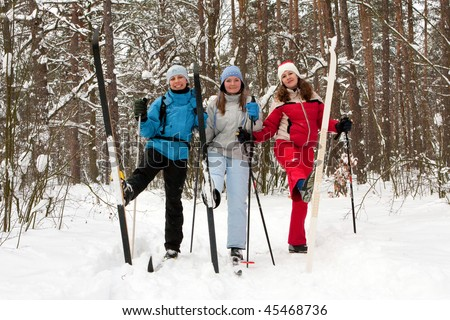 three beautiful girls in the winter woods on cross-country skiing - stock photo