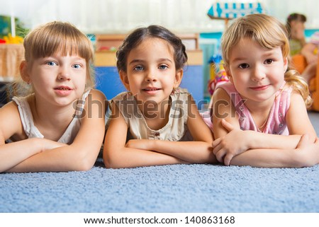 Three beautiful girls lying on floor at daycare - stock photo