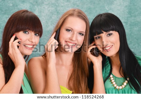 three beautiful girls  on a green with a mobile phone - stock photo